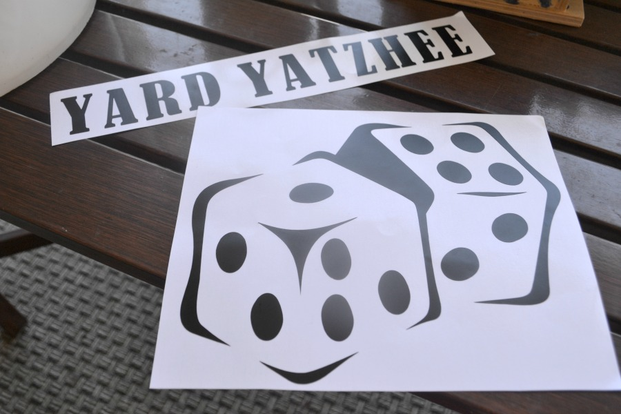 """Vinyl cut outs of black dice and the words """"yard yatzhee"""" on a white background"""