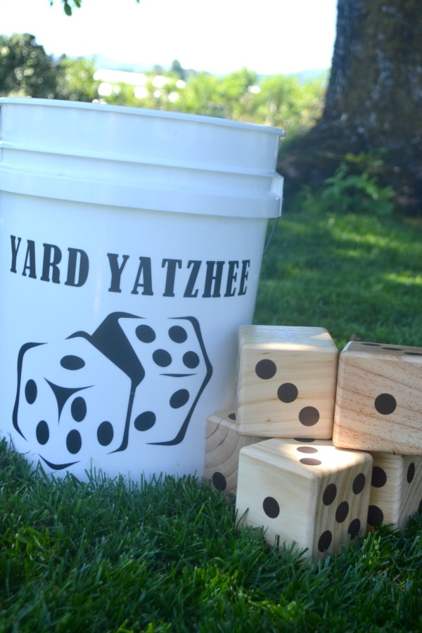 """A white bucket with a picture of black dice and the words """"yard yatzhee"""" on it sitting next to a stack of wood dice in the grass"""