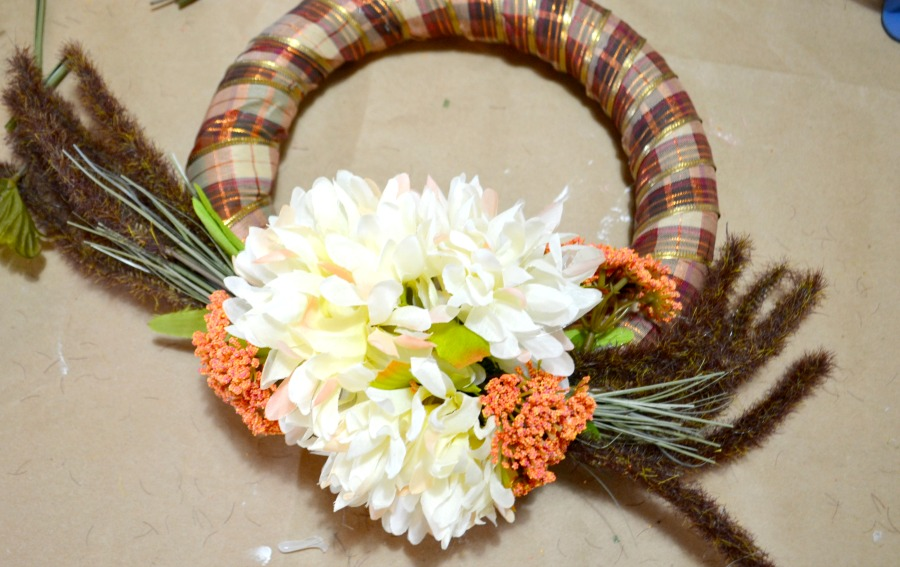 A fall wreath with faux flowers sitting on butcher block paper