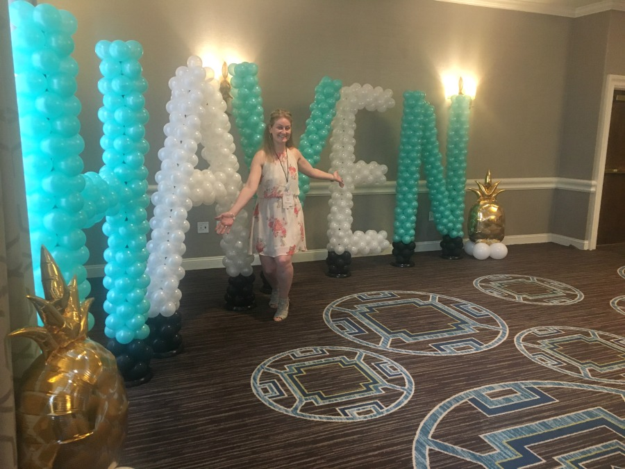 Tall balloon letters in teal and white spelling out Haven with me in front posing