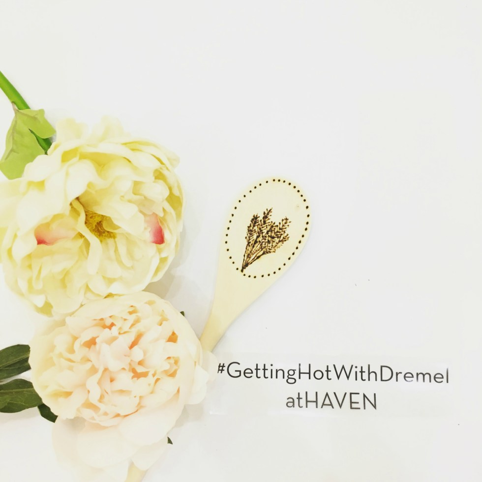 A flatlay photo of faux peony flowers on the right side against a white background with a wooden spoon etched with lavender like flowers