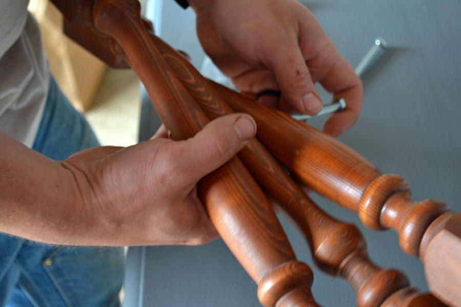 Three brown stair spindles being held while a bolt is placed through all three
