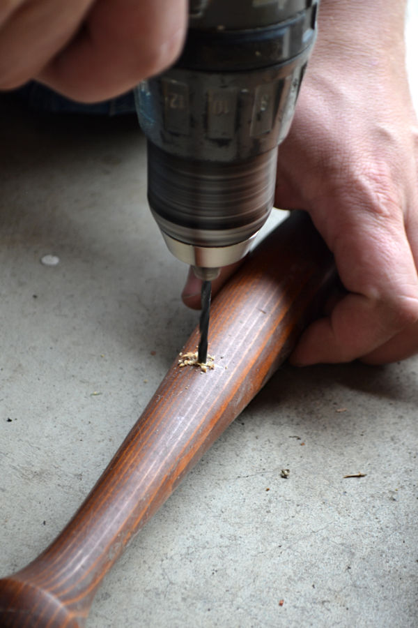 A drill bit being drilled through a brown stair spindle on a concrete floor while a hand holds the spindle