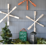 Three spindle snowflakes hung on a house with a small Christmas tree in front and a bench with Christmas greens and a lantern