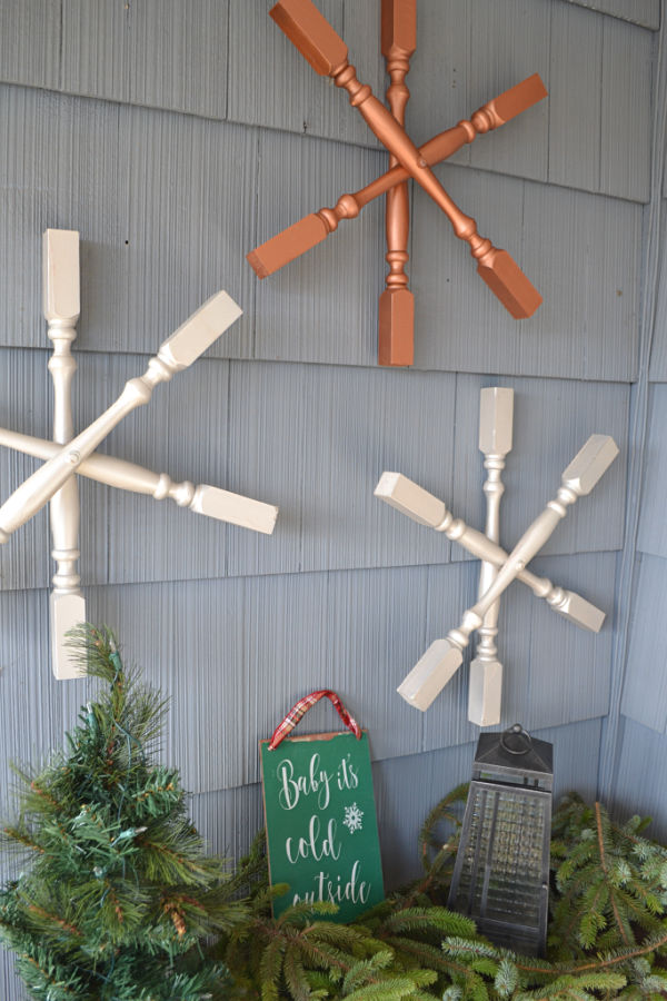 Stair spindles turned into snowflakes and displayed on the side of a blue house with evergreen greenery below