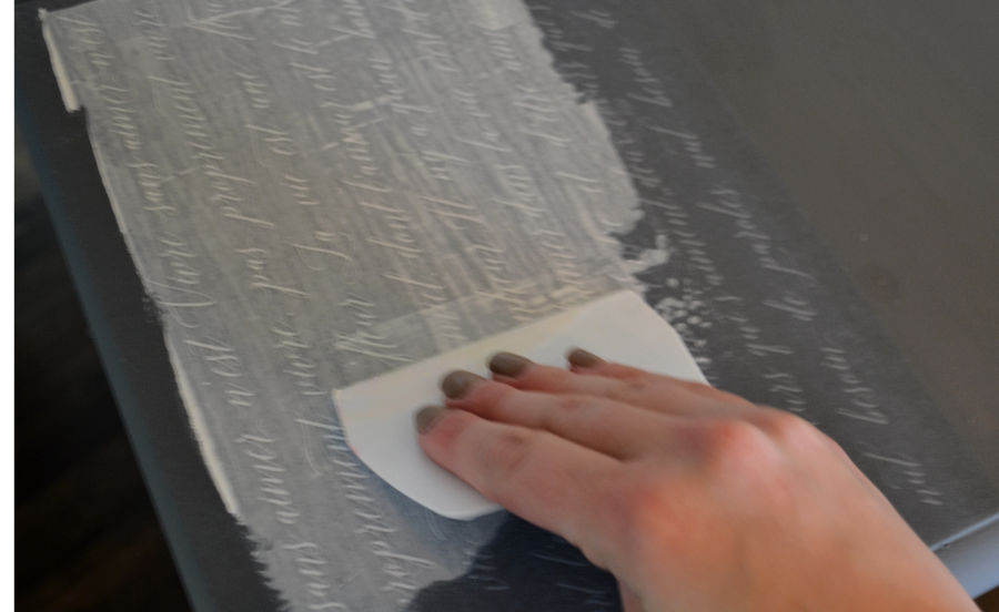 A woman's hand using a spreader to push chalkart through a mesh stencil with french script