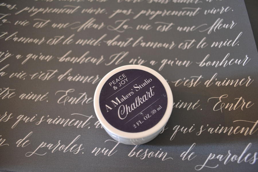 French script on a gray background with a small tub of ChalkArt in Peace & Joy sitting unopened on top