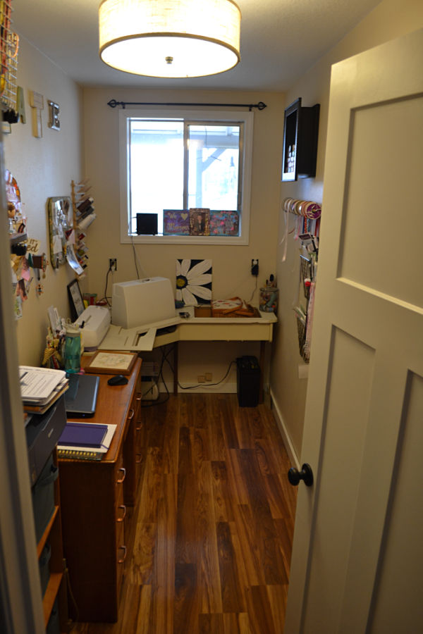 A view from the door looking into a craft room with a desk and sewing table against the left side of the room