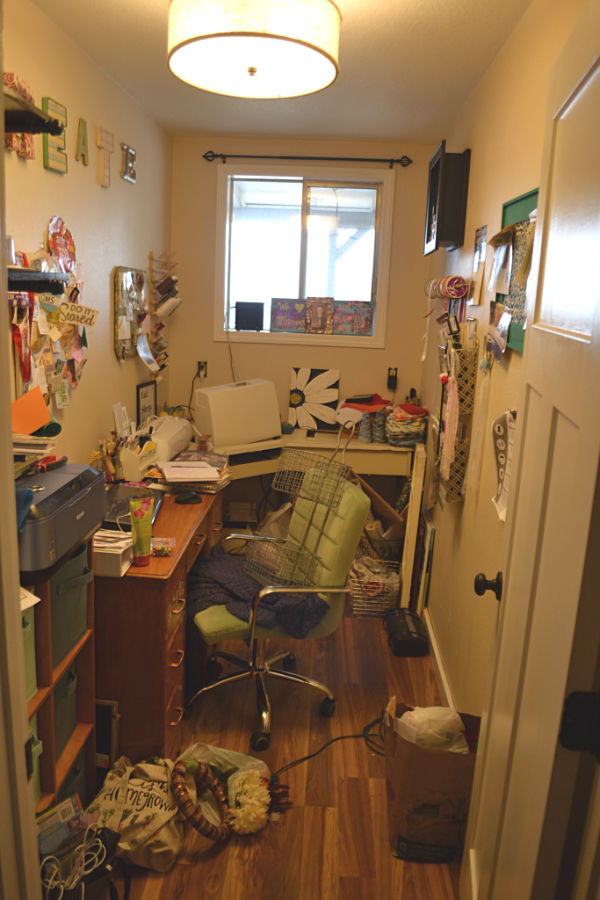 A craft room and office with multiple desks and clutter on all surfaces and the floor