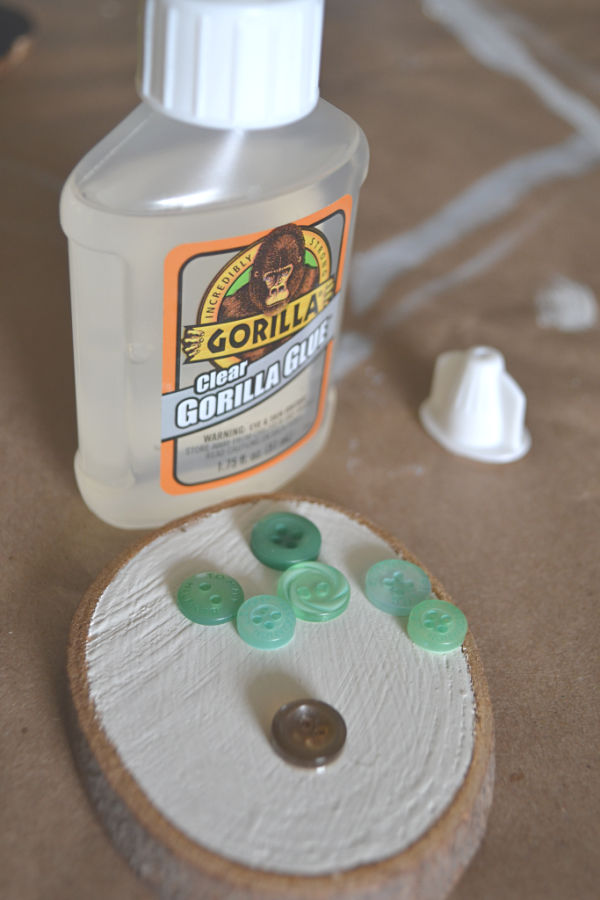 A clear bottle of Gorilla Glue with the cap sitting next to it and a white painted wood slice in front with green and brown buttons in random display before being glued down