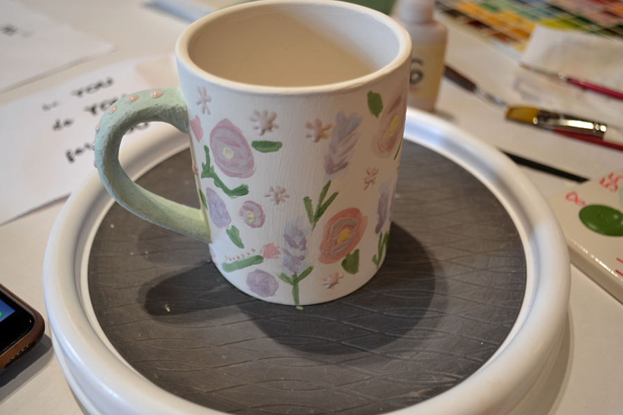 A white mug with pink and purple flower assortment with a green handle on a lazy susan