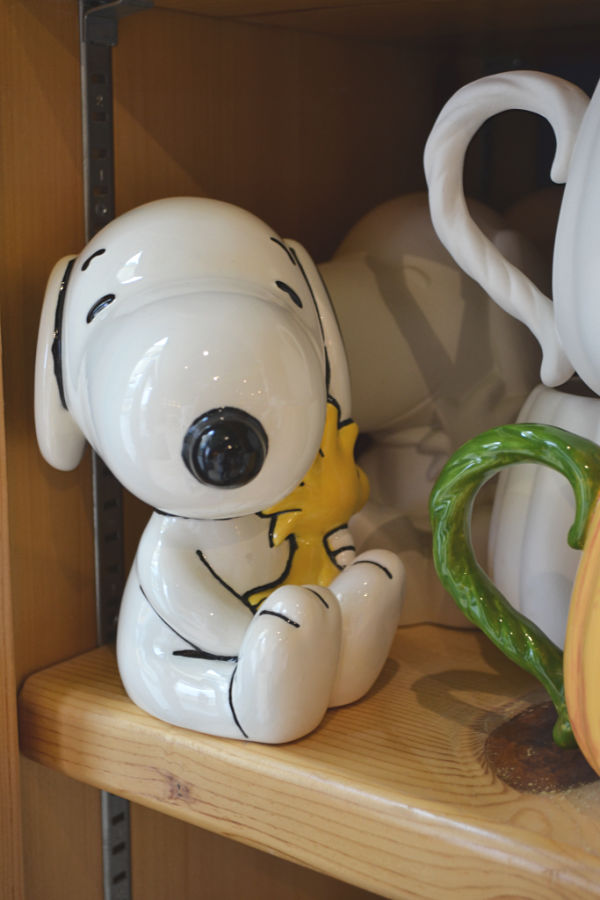 A ceramic painted snoopy and woodstock sitting on a shelf