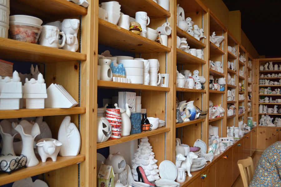 A wide view of unpainted ceramic pieces sitting on shelves in a studio