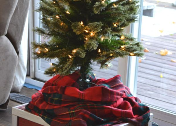 A wider view of a red and ivory wooden box with a pencil thin Christmas tree sitting on top with a plaid cloth