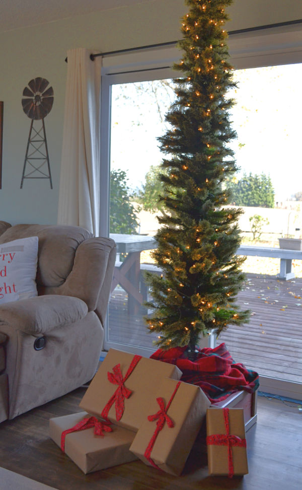 A pencil thin Christmas tree with white lights in a living room in front of a window with brown wrapped presents wrapped in red ribbon sitting on a red and ivory wood box