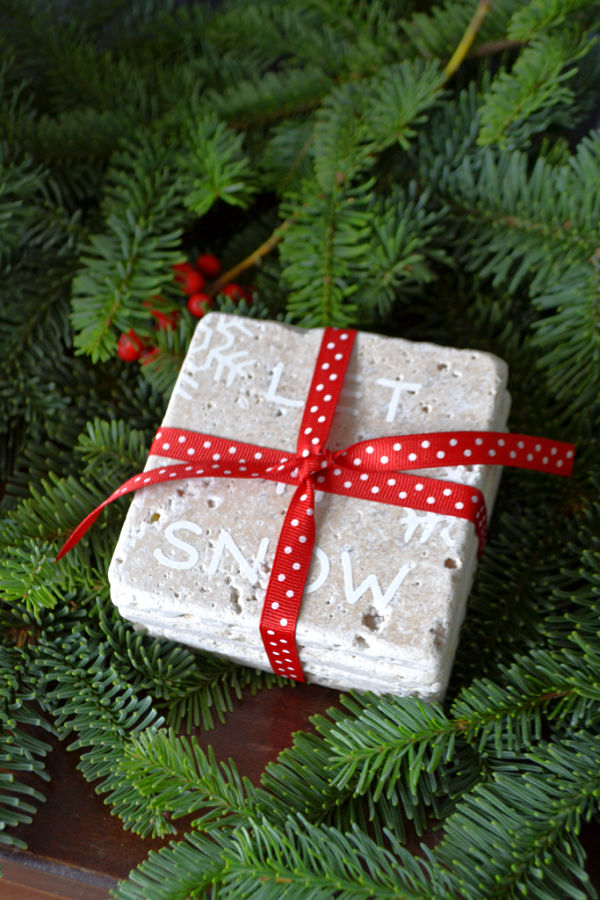 A stack of four travertine tiles with Let it Snow on the top one tied up with red ribbon with white polka dots