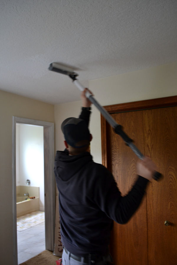 A man painting a bedroom ceiling white with a twist paint stick