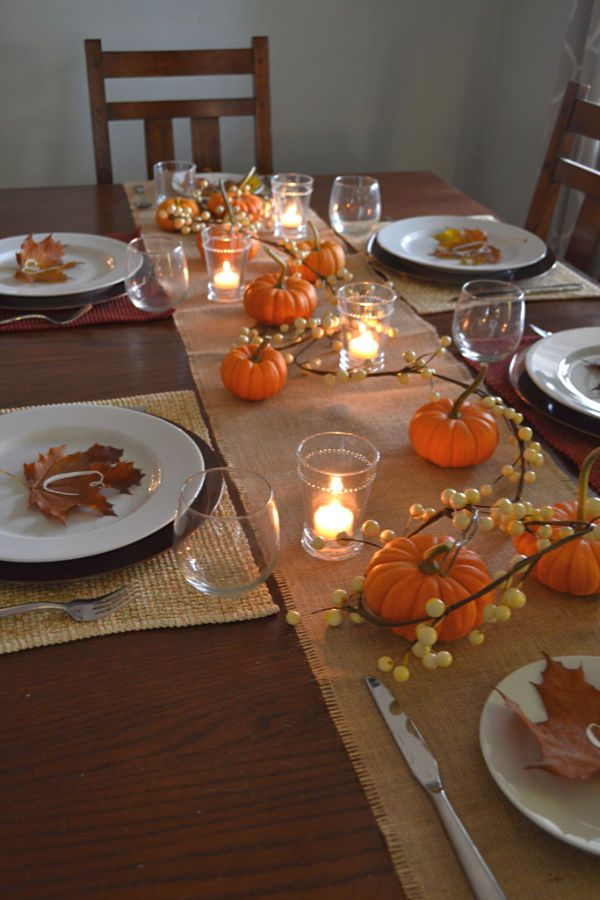 A dark wood table with a burlap runner with small pumpkins, candles and garland down the center with white plates and maple leaves with letters