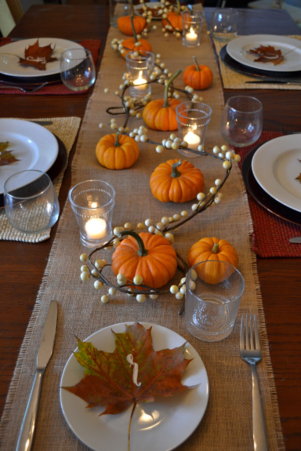 An above view of a table with a burlap runner, pumpkins, white berry gardland with candles in glasses and white plates with maples leaves with initials in white