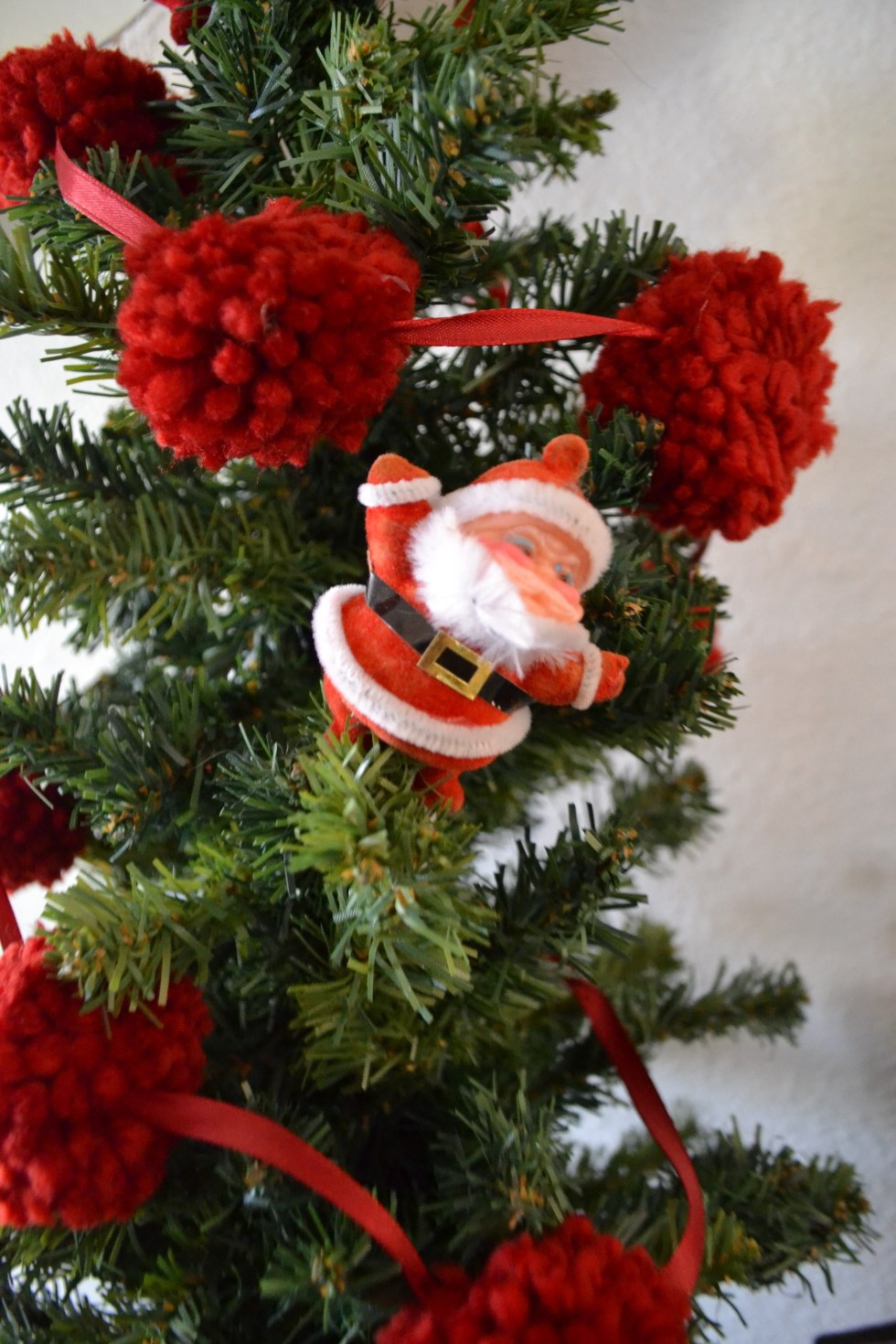 A vintage Santa is displayed in a fake Christmas tree with red yarn pom pom garland