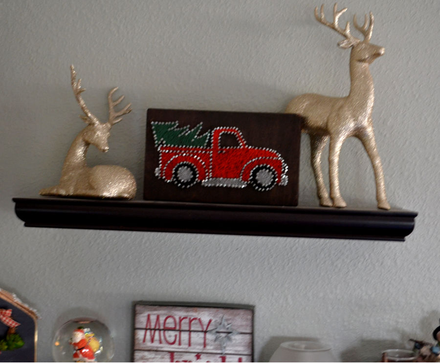 A floating shelf with 2 glittered deer and a red truck string art in the center
