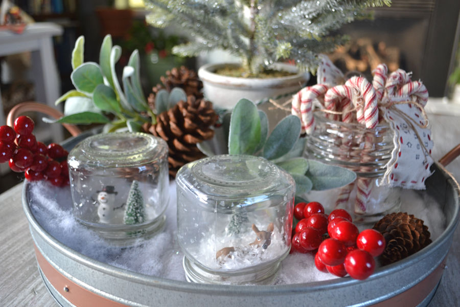 "A close up of ""snow globes"" tucked into fake snow along with berry picks, lambs ear picks and pinecones"