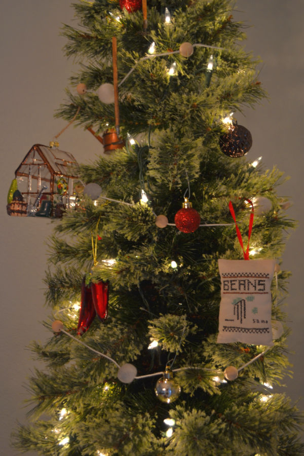 A thin pencil tree with white lights, a string garland with felt balls and wood balls, a glass greenhouse on the left and several red and brown Christmas ball ornaments and a cross-stitched beans pillow ornament