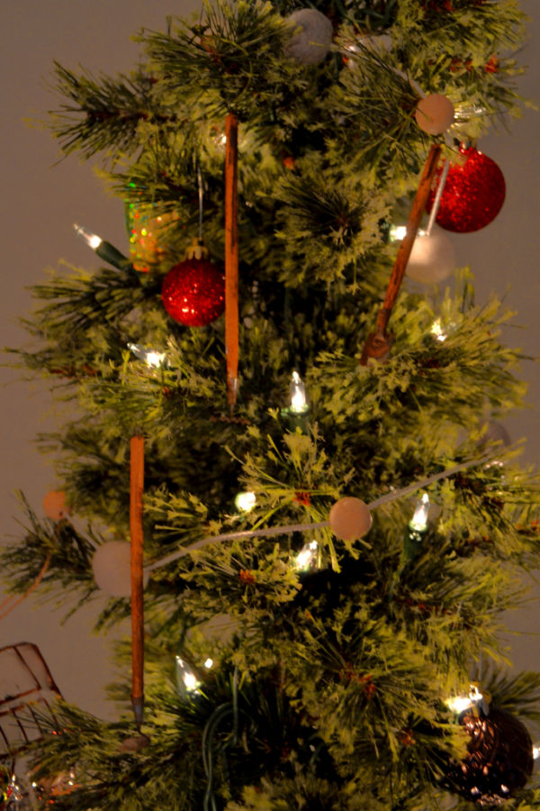 A close up of a pencil tree with a hoe, shovel and rake ornament hanging between some red glitter balls and felt ball garland