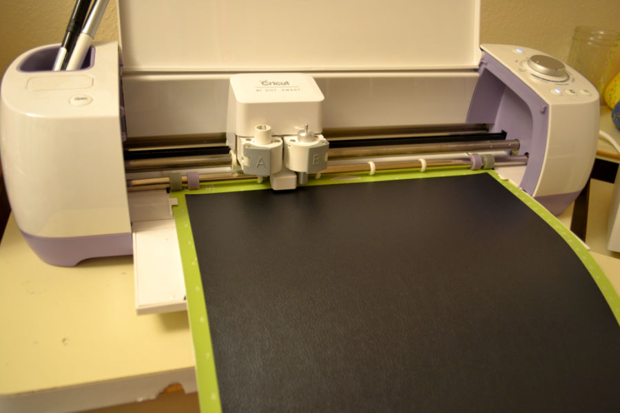 A cricut cutting machine being used to cut faux leather that is dark blue in color