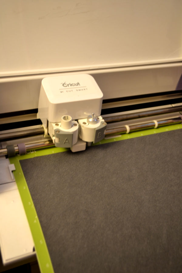A Cricut machine cutting close up with faux leather sheet on a cutting mat face down