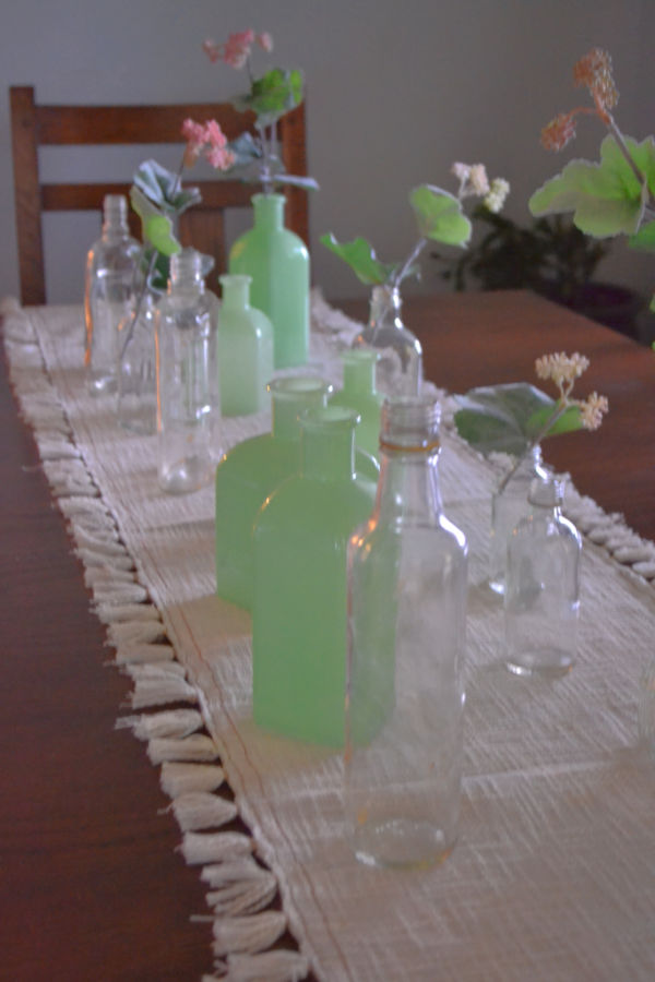 A close up view of a white linen tablerunner with light green milk glass pieces and clear vintage bottles with faux small coral flower picks nesting in some of the bottles along the tablerunner