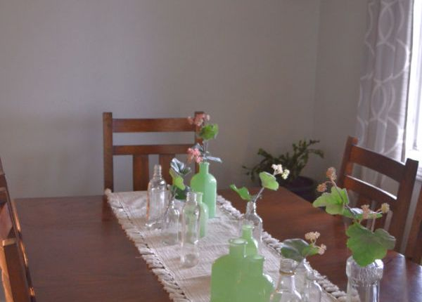 A dark brown table with a white table runner with tassels with vintage clear glass bottles intermixed with green milk glass bottles down the table with faux green coral stems