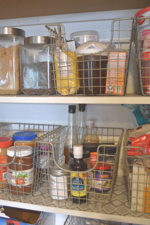 A close up of several scoop wire baskets next to each other in on pantry shelving containing dry goods and oils and vinegars