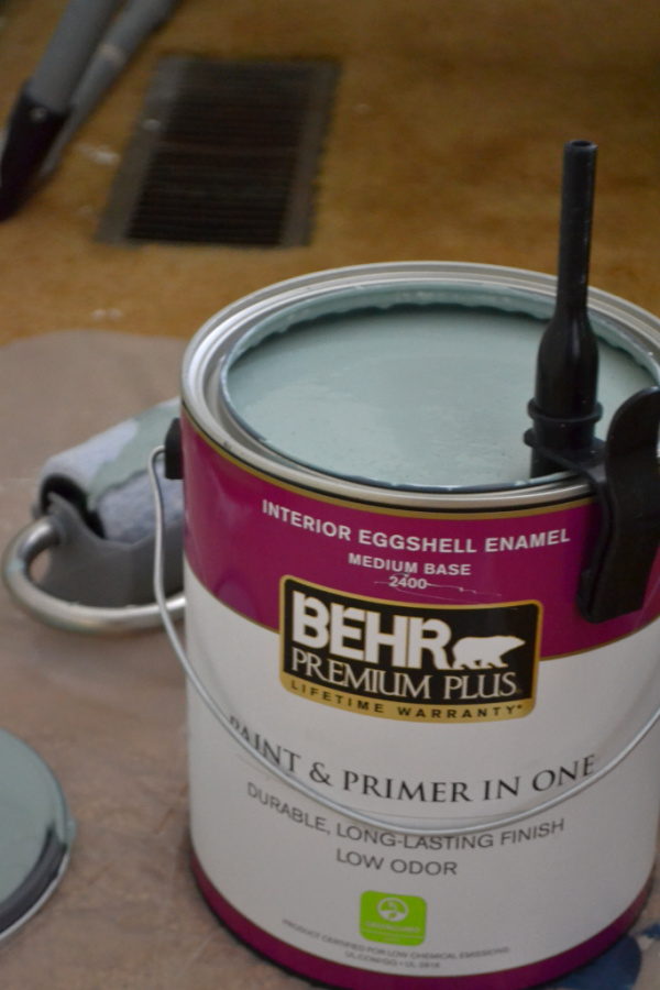 A can of Behr paint with a partial roller image behind it and a plastic pipe stuck to the can and into the paint