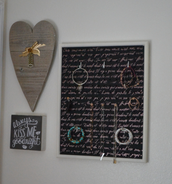 """A gallery wall with a wooden heart, a sign that says """"always kiss me goodnight"""" and a rectangular jewelry wall organizer with jewelry hanging from the pegs"""