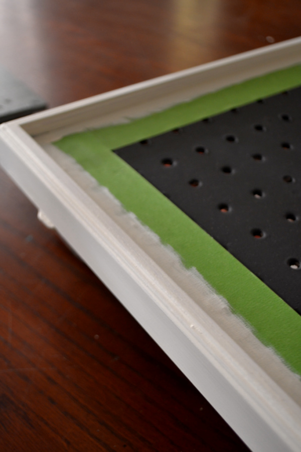 A close up of a white painted frame and a black painted pegboard with green Frogtape on the black surface to keep the white paint seperate when painting