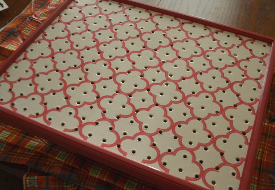 A pink frame with a pink and white pegboard laying on a brown table