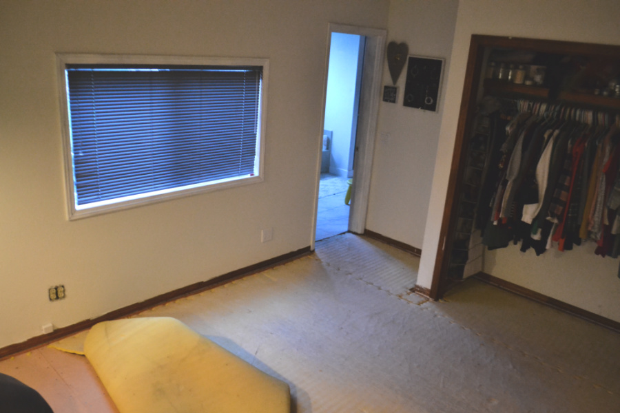 Viewing into a bedroom with part of the closet showing on the right, blue metal blinds covering a window on the left, carpet pad in a pile on the lower left