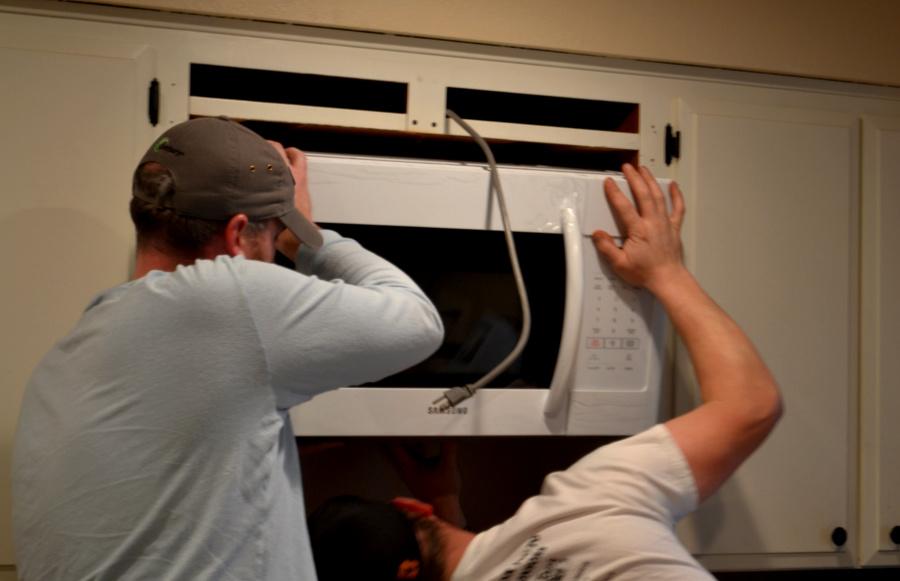 Two men one below and one on the left of the microwave as they lift it into place above a stove range