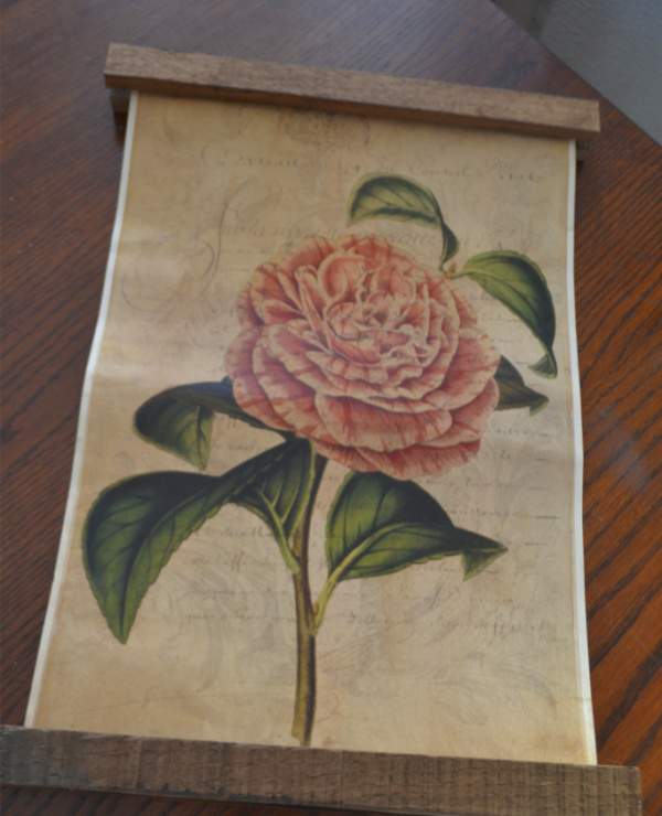 A vintage floral print laying on a dark wood table with scrap wood trim at the top and bottom of the print