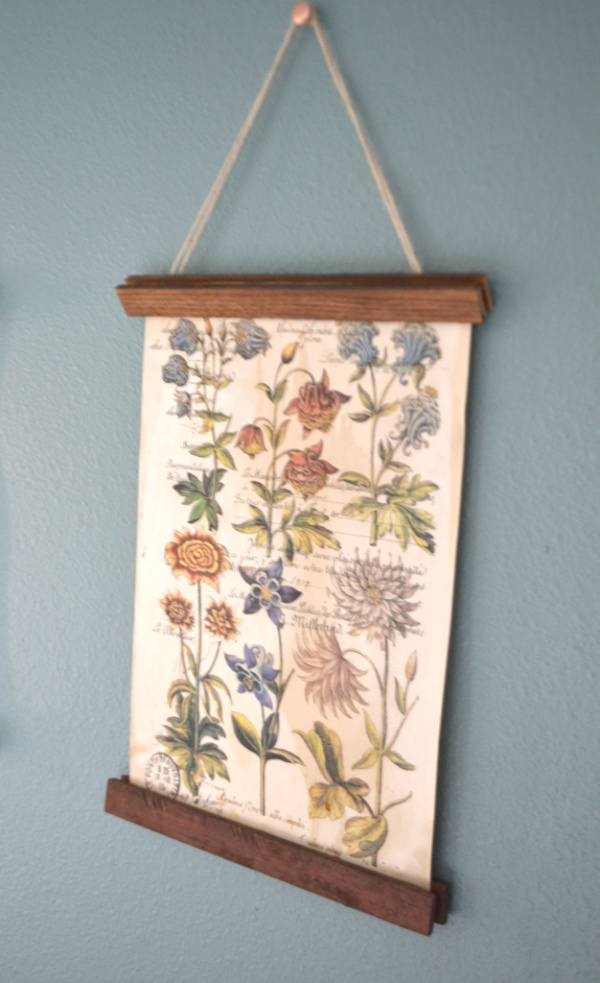 A close up of a flower print being hung on a wall with wood trim at the top and bottom