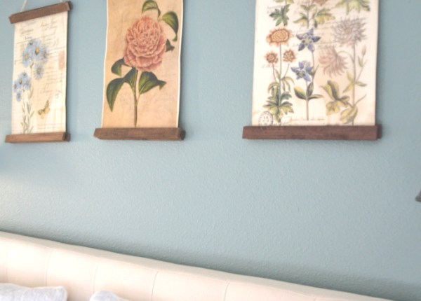 Three vintage floral prints being hung over a headboard against a teal wall