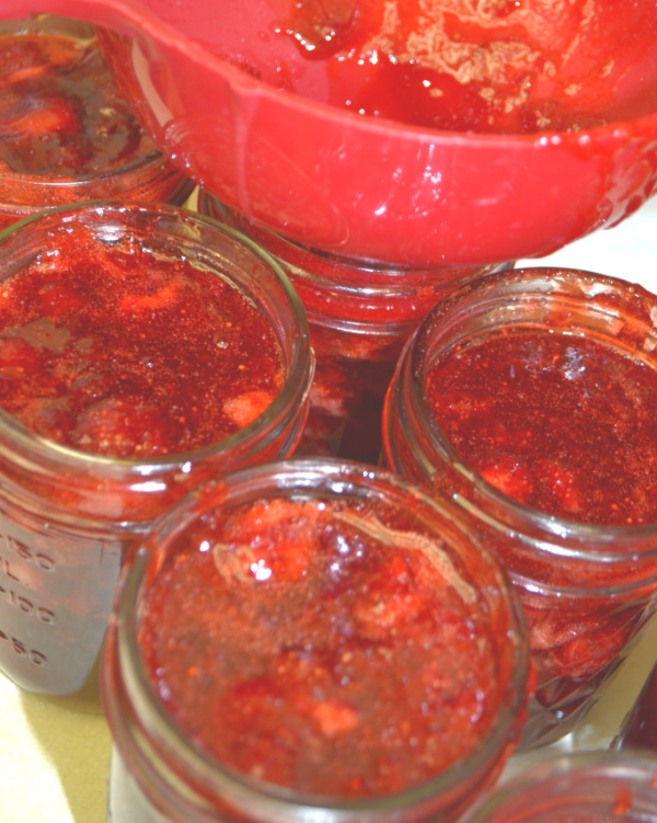 An above view of glass jars filled with strawberry jam and a red funnel in one jar