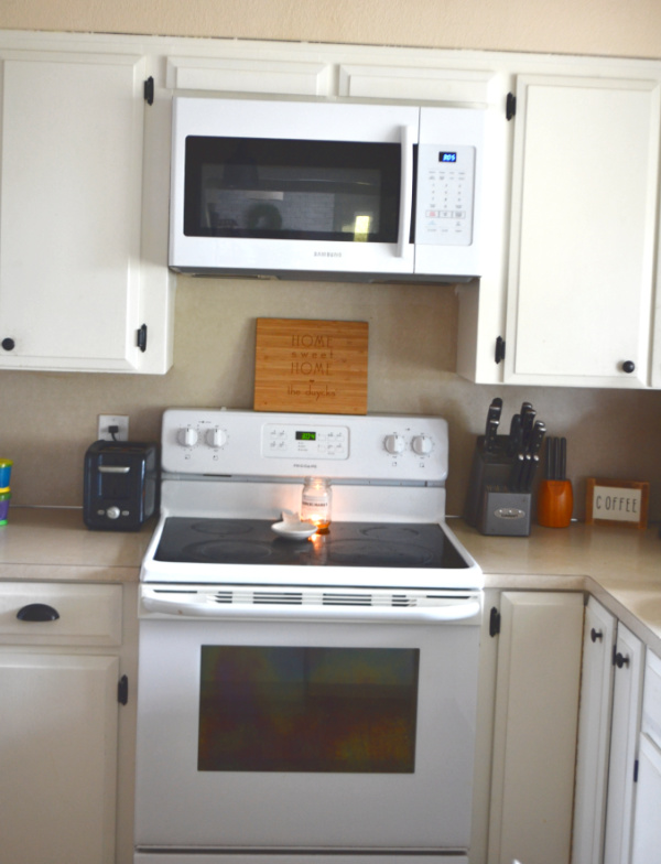 A final view of white cabinets in a kitchen with a white glass top range below a white microwave install over the range