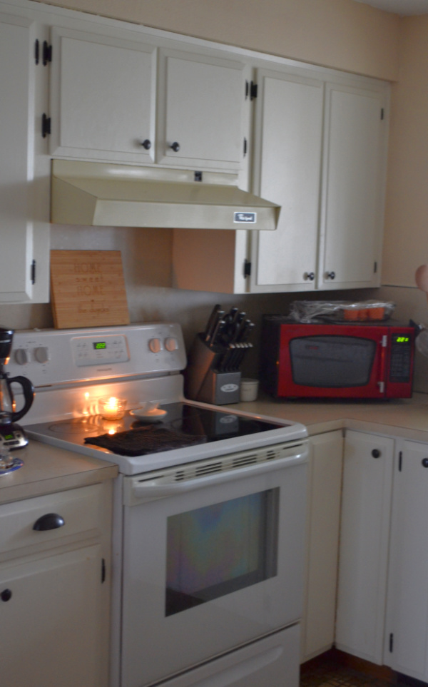 White cabinets in a kitchen surround a stove with a candle burning and a vent hood above the stove with a red microwave sitting on the counter
