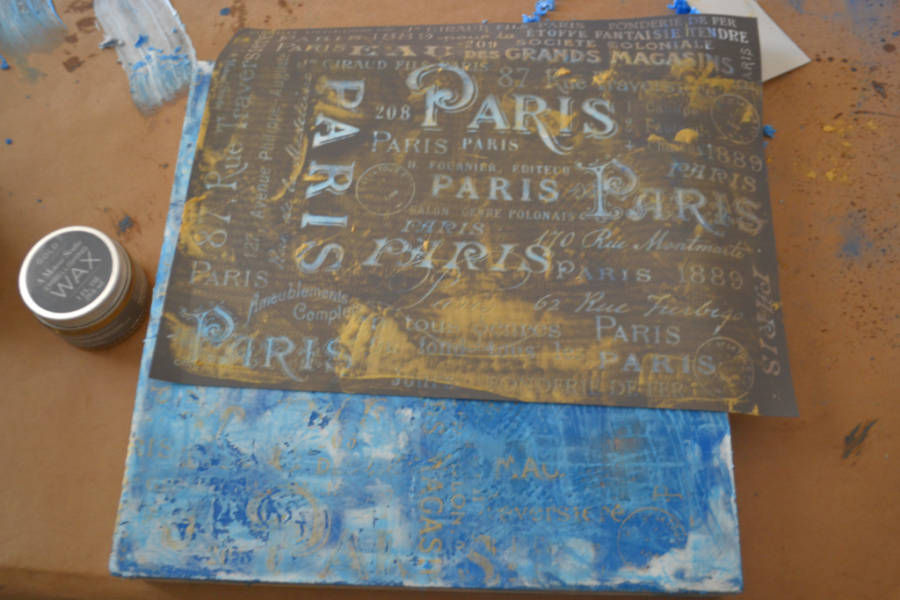 A Paris stencil with gold embellishing wax on the surface being pressed through the stencil onto the blue/white wax art