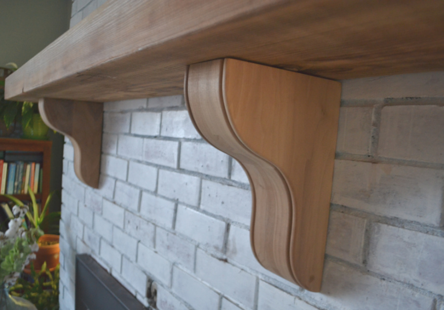 A close up picture of solid walnut corbels under a solid wood mantelpiece