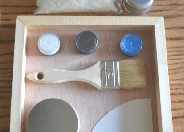 An arrangement of a brush, metal container, blue, black and white pigment containers and a plastic spreader sitting in a wood surface