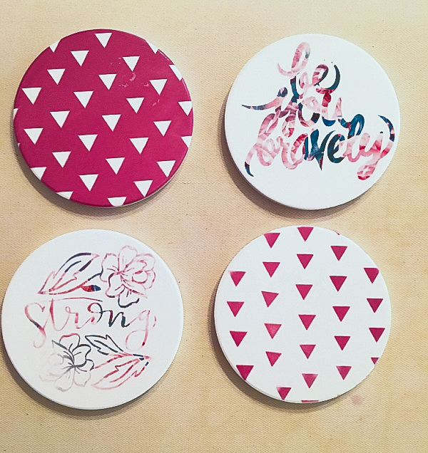 "A set of 4 white ceramic coasters from above, one with the words-""be you bravely"" ink flowers, ""strong"" with flowers and pink triangles"