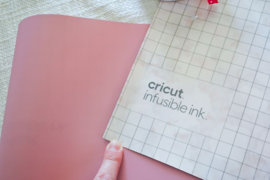 A gridded backing of a Cricut infusible ink sheet on top of a pink infusible ink image with a person's finger holding onto them